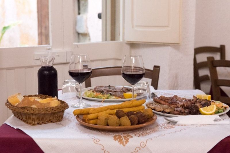 redattori licheri zonzi tavola con crocchette, vino e carne